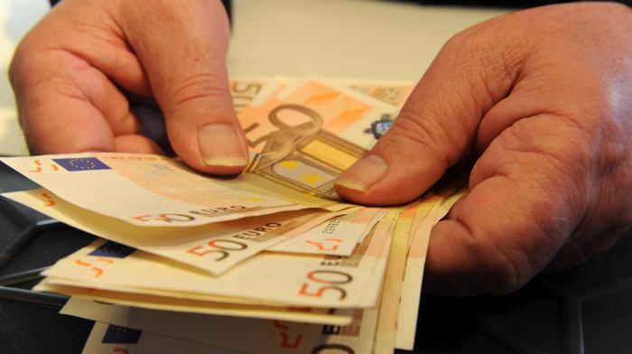 Una persona conta alcune banconote in una banca, Pisa, 15 maggio 2012. ANSA / FRANCO SILVI